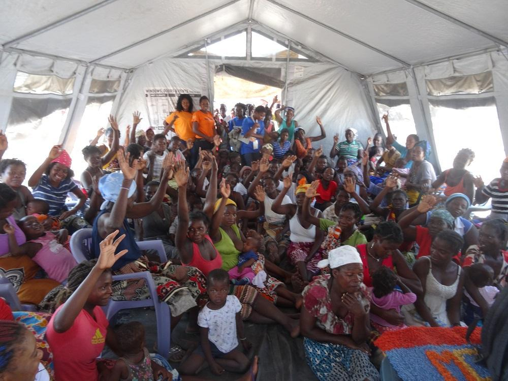 Women in a Mozambican resettlement camp raise their hands to indicate they had no warning that Cyclone Idai was about to strike